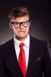 Troubled young business man. Bitting his lips and raising an eyebrow, over dark background stock photo