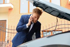 Troubled young businessman talking on phone near broken car. Outdoors royalty free stock image