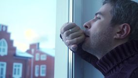 Troubled young man with grey hair looking through the window. Clip stock video footage