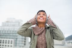 Troubled young model in winter clothes clogging her ears. Outside on a cloudy day Royalty Free Stock Photography