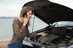 Troubled young woman talking on phone near broken car. Outdoors stock photography