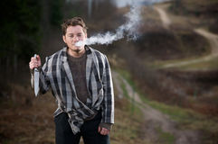 Troublemaker man. Young man in unkempt layered clothing, blowing cigarette smoke from his mouth, holding a knife at chest level in his right hand.  Taken in a Stock Photo