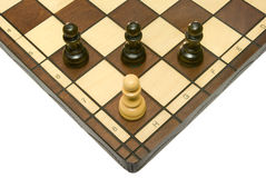 Troubles. Pawns (three black and one white) on a chess board. A white isolated background Stock Photo