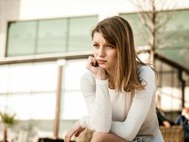 In troubles - depressed young woman. Depression - portrait of young worried woman oudoor in urban environment Royalty Free Stock Photography