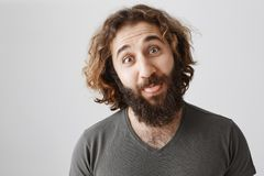 Troubles fear of laugh. Indoor shot of carefree attractive easter guy with curly hair and beard showing tongue and. Making funny face while standing over gray Stock Photo
