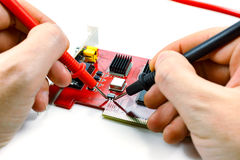 Troubleshooting DVR motherboard with a multimeter on a white background Royalty Free Stock Photos