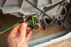 Troubleshooting electrics in the washing machine. Services of the handyman stock photos