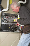 Troubleshooting Furnace Problems. Repairman servicing or repairing basement furnace unit Stock Image