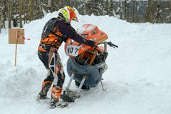 Troubleshooting. GOLYGINO, SERGIEV POSAD DISTRICT, RUSSIA - FEBRUARY 10, 2018: Unidentifiable athletes on a snowmobile moving in the winter forest participates royalty free stock image