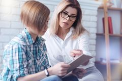 Troublesome youngster giving his answers during psychological test. Fill the blank space. Serious women pointing at a clipboard held by a teenage boy passing a Royalty Free Stock Images