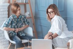 Troublesome youngster looking at laptop during psychotherapy session. Have a look. Female therapist asking a problem boy to look at a screen of her laptop while Royalty Free Stock Images
