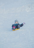 On the trough for driving on snow hill child travels at high speed Royalty Free Stock Photography