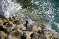 Troughs and holes in the rock eroded by water. Wave of water eroding the rock at sea shores Royalty Free Stock Images