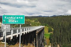 Trous de balle de l'Alaska dans le panneau routier pour le Br de rivière de Kuskulana images stock