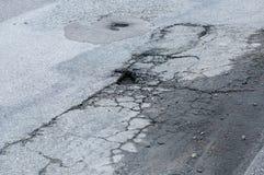 Trous de pot de Secveral dans la route goudronnée nécessitant l'entretien Images libres de droits