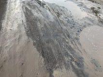 Trous et magmas sur la route cassée photo stock
