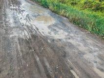 Trous et magmas sur la route cassée photos stock