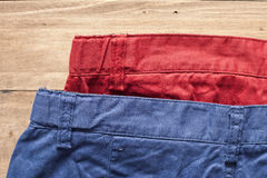 Trousers. Red and blue casual trousers on a wood surface Royalty Free Stock Images