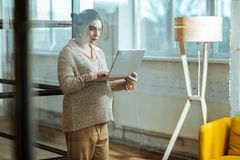 Pregnant woman wearing beige trousers and sweater holding laptop. Trousers and sweater. Pregnant successful woman wearing beige trousers and sweater holding stock photo