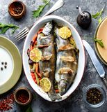 Trout with bacon and vegetables. Trout with bacon baked in the oven. Fish with vegetables royalty free stock image