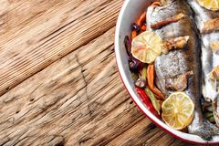 Trout with bacon and vegetables. Trout with bacon baked in the oven. Fish with vegetables royalty free stock images