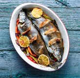 Trout with bacon and vegetables. Fish with vegetables and lemon.Delicious trout fishes baked with bacon stock photos