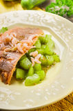 Trout with braised cucumber and shrimp in white plate Stock Photos