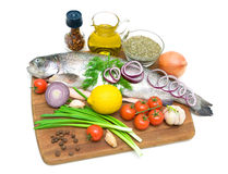 Trout and different food on a cutting board on a white backgroun Stock Image