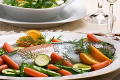 Trout dinner. Organic whole trout cooked with vegetables, green salad and glass of wine served for dinner stock photo