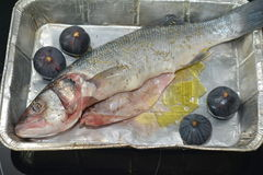 Trout with figs. In bakeware for roasting royalty free stock image