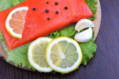 Trout fillet with lemon, garlic and lattuces leaves Stock Photo