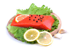 Trout fillet with lemon, garlic and lattuces leaves on white Stock Image