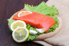 Trout fillet with lemon, garlic and lattuces leaves Stock Images