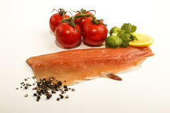 Trout fillet with lemon, tomato and peppercorn. Raw trout fillet with slice lemon, wet tomato crushed peppercorn and fresh coriander on white Royalty Free Stock Photo