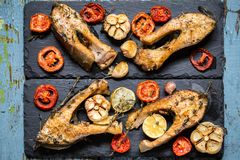 Trout fish with baked vegetables, garlic, thyme, tomatoes Stock Photo