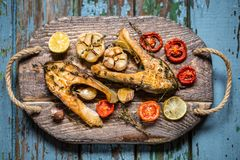 Trout fish with baked vegetables, garlic, thyme, tomatoes Royalty Free Stock Images