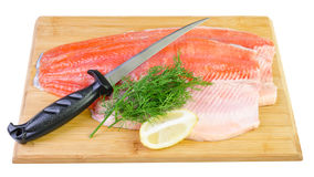 Trout fish fillet with knife on a kitchen board Stock Image