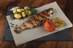 Trout fish fried. With young potato on slate surface. wooden background Stock Images