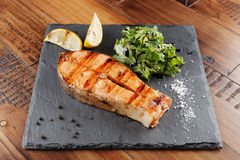 Trout fish steak. With lemon on a shale surface. wooden background Royalty Free Stock Photo