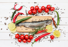 Trout fish on wooden cutting board with cherry tomatoes Stock Photos