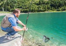 Trout-fishing on mountain lake Stock Photos