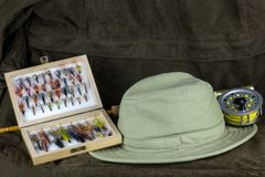 b1896b1a48554 Fly Fishing Rod with Fly Box and Hat on Outdoor Coat royalty free stock  photography