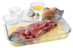 Trout with ham. Fresh trout with slices of ham on a layer potatoes and all the ingredients necessary for its preparation to the oven Stock Image