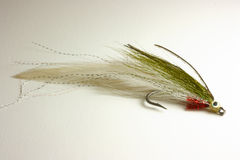 Trout lure for fly fishing. Hand tied minnow fishing fly for trout or bass fly fishing stock photo