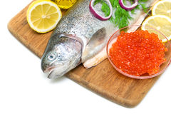 Trout, red caviar, lemon and vegetables on a cutting board close Stock Images