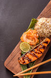 Trout with rice. Trout with japanese salad, rice and lemon on a wooden board Royalty Free Stock Photography