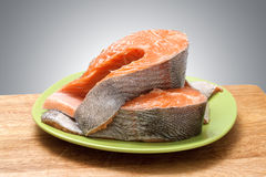 Trout steak on green dish. On wooden plate. red fish Stock Photography