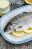 Trout stuffed with lemon slices and seasoned with aroma sea salt with lemon peel Stock Photo