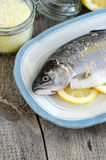 Trout stuffed with lemon slices and seasoned with aroma sea salt with lemon peel Stock Images