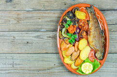 Trout with vegetables on a clay plate Royalty Free Stock Image